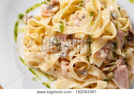 Tagliatelle pasta with ham, mushrooms and yolk. Selective focus. Pasta Carbonara on white plate with parmesan. Italian pasta food concept. on a white plate, the dish is served in the restaurant