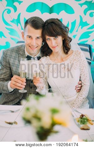 The close-up portrait of the hugging newlyweds holding the champagne glasses