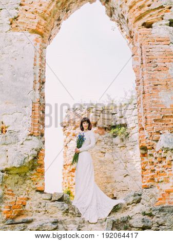 The full-length view of the thoughtful bride with the flowers standing on the ruins of the house