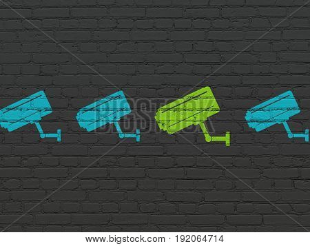 Protection concept: row of Painted blue cctv camera icons around green cctv camera icon on Black Brick wall background