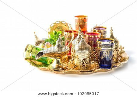 Golden tea service and green mint leaves on white background. Ramadan. Eid Mubarak