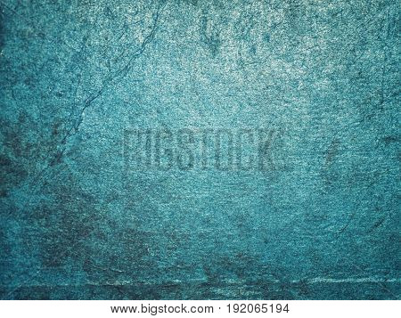 Cracking and peeling blue paint on a wall. Vintage wood background with peeling paint. Old board with Irradiated paint