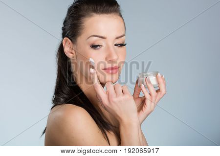 Young Beautiful Woman Moistening Face With Cream