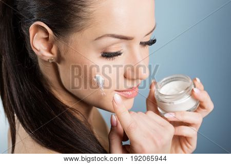 Beautiful Woman Moistening Face With Cream