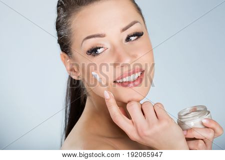 Beautiful Smiling Woman Moistening Face With Cream