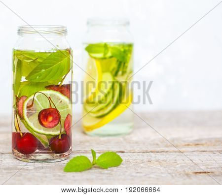 Citrus cherry and herbs infused sassi water for detox or dieting in glass bottles. Clean eating weight loss healthy lifestyle concept