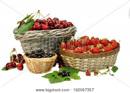 Summer gifts: cherries strawberry and black currant in wicker baskets isolated on white.