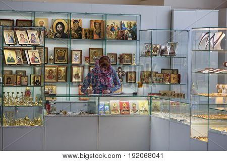 ST.PETERSBURG/ RUSSIA - JUNE 17, 2017. Orthodox shop inside of church. Woman in the headscarf behind the counter selling the religious utensil, candles and icons . Russia.