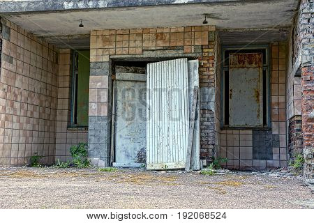 Bolted windows and a wooden door on the facade of an abandoned building