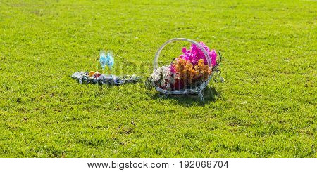 Glasses for wine and flowers in basket in summer day.
