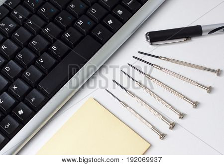 Keyboard Pen Note Paper and Screwdrivers on the Desk