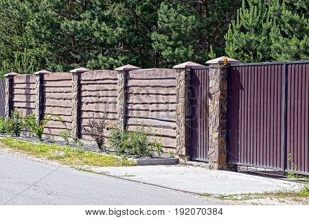 Gray brown gate and a fence in front of the asphalt road
