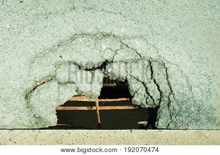 Dangerous hole on the bridge with steel reinforcement. Close up. Selective focus. Damaged bridge.