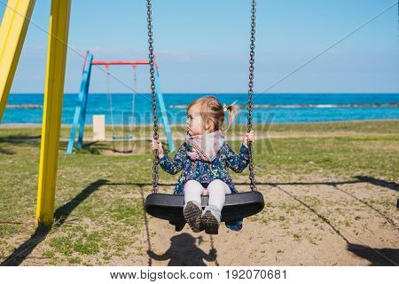 Little baby girl fly with fun on rope swing on sea beach with waves and surf in tropical island. Baby, people activity on summer family vacation with child