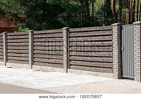 Gray brown gate and wooden fence in front of an asphalt road