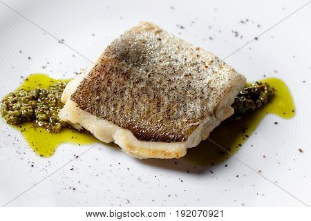 Fried fish fillet, Atlantic cod with rosemary in white plate. green sauce of herbs. On a white plate, the dish is served in the restaurant.