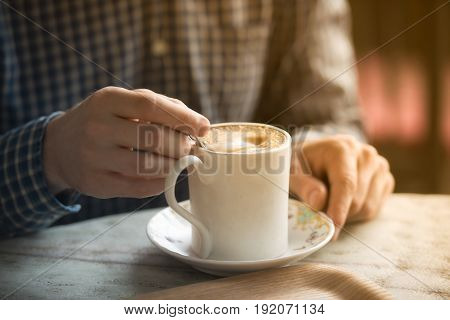 Cup of morning cofee in mans hands on wooden table