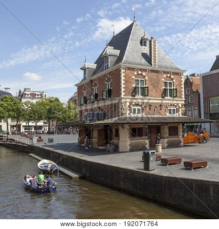 Leeuwarden Netherlands 11 june 2017: young people in boat pass waag building in centre of dutch town leeuwarden which will be european cultural capital in 2018