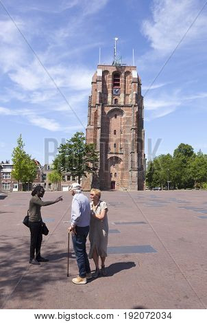 Leeuwarden Netherlands 11 june 2017: young black man talks to older couple near old lopsided tower oldehove in the center of ancient city Leeuwarden in the netherlands
