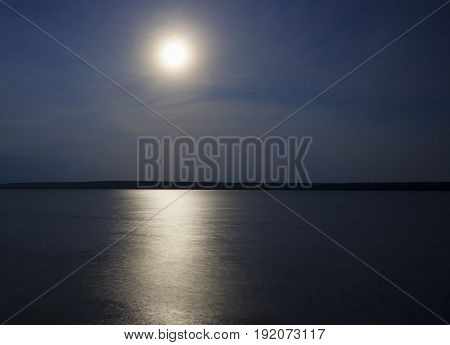 Bright moon and its reflection on Dore Lake in Saskatchewan