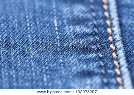 Blue Jeans Cloth Background Texture With Yellow Seam Close Up.