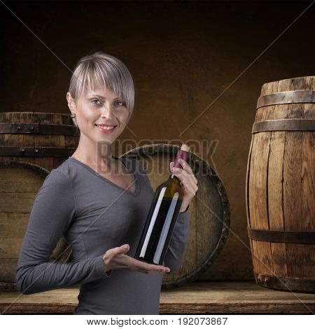 Young barefoot girl holding straw basket with a bottle of wine over natural background.