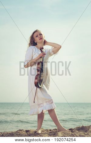 Music love hobby and everyday passion concept. Woman on beach near sea holding violin