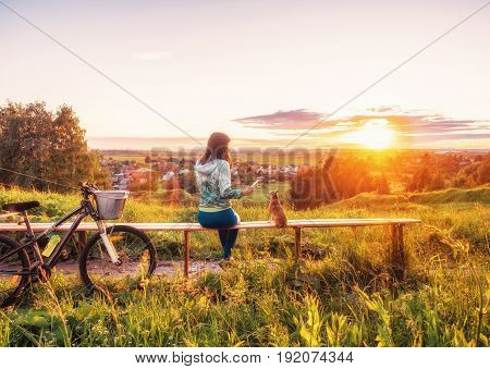 A young girl is looking into the phone. A girl is taking pictures of a dog on a smartphone beautiful sunset. Walking with a dog on a bike in the evening.