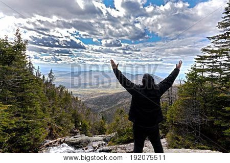 Man in praise while looking out from elevation on Mount Washinton via Ammonoosuc ravine trail in Coors County New Hampshire.