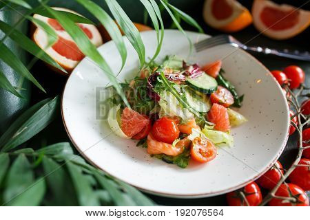 Vegetable salad with grapefruit and salmon over greeb background