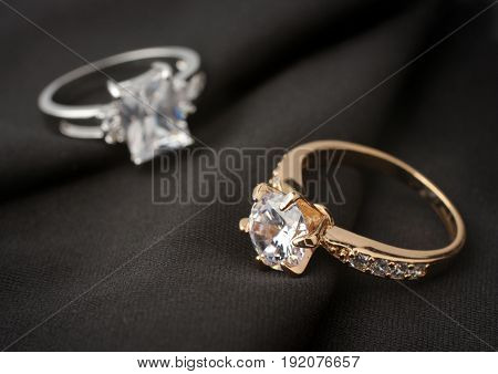 two jewelry rings with diamonds on black cloth