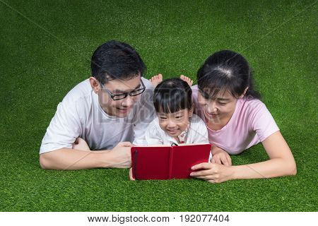 Asian Chinese Parents And Daughter Reading The Book