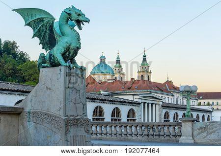 Green dragon on Dragon bridge in Ljubljana with market and church of Saint Nicholas
