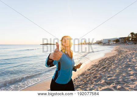 Motivated sporty woman doing thumbs up success gesture after urban workout on seashore