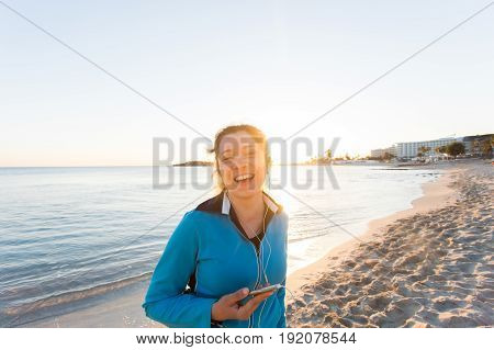 sport and lifestyle concept - woman after running with earphones outdoors.