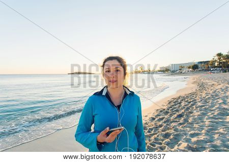 Outdoor sport, fitness gadget and people concept - Smiling female fitness holding smartphone with earphones
