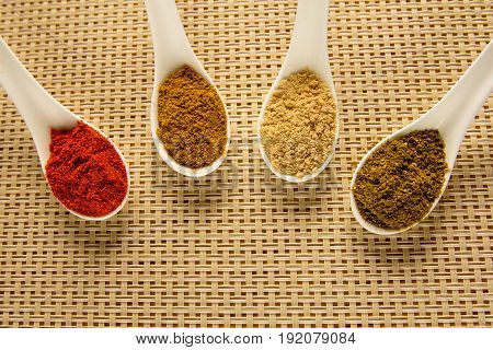 Spices in spoons on the table. Seasoning in powder.