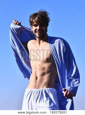 Bearded man short beard. Caucasian smiling happy macho with moustache and ruffled hair in blue striped pajamas showing strong torso with six packs on blue sunny sky background