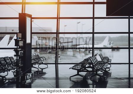 Airport hall with: empty rows of black seats huge panoramic windows boarding airplanes in background reflective tiled floor vertical mock-up of information display moody rainy weather outside