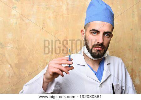 Medic Syringe In Hand Of Bearded Doctor