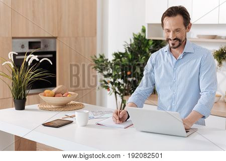 Pleasant work. Young bearded man standing behind the kitchen counter, working on the laptop and writing out something from it into the notebook while smiling