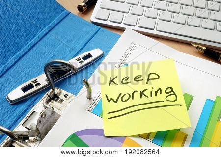 Keep working sign on a piece of paper and documents.