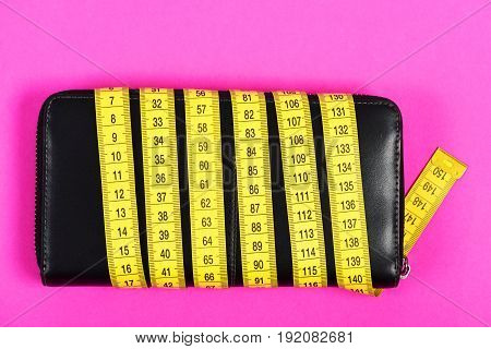 Female Purse In Black Color Wrapped With Yellow Flexible Ruler