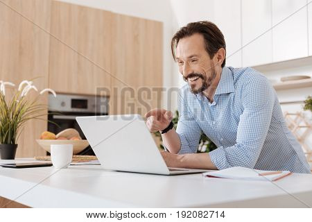 Amusing content. Handsome bearded man standing behind the kitchen counter, looking at the laptop and pointing at it with his finger while laughing.
