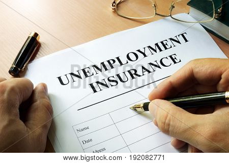 Unemployment insurance form on a table and pen.
