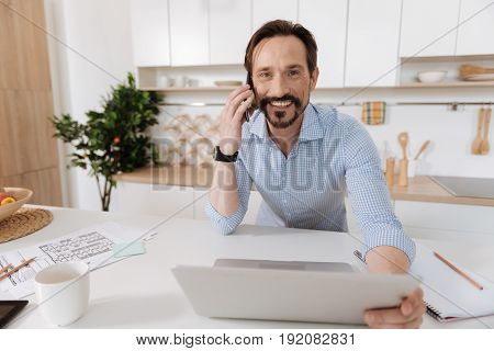 Pleasant negotiations. Young bearded man standing in the kitchen, talking on the phone while holding the laptop screen with one hand and smiling at the camera