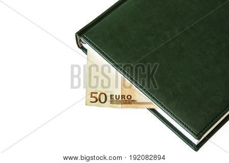 Between the sheets of the closed diary is visible part of the bill of 50 euros