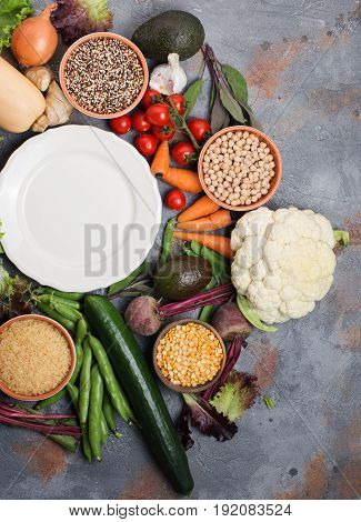 Vegetables and grains, with off white plate, broccoli, squash, beans, tomatoes, carrots, avocado, top view, vertical selective focus