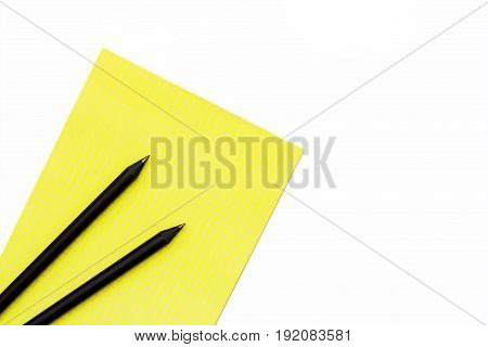 Two Black Pencil And A Yellow Notepad On A White Background. Minimal Concept Workplace At The Office