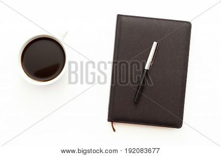 A Cup Of Black Coffee And A Day Planner With Pen On White Background. Flat Lay Minimal Business Conc
